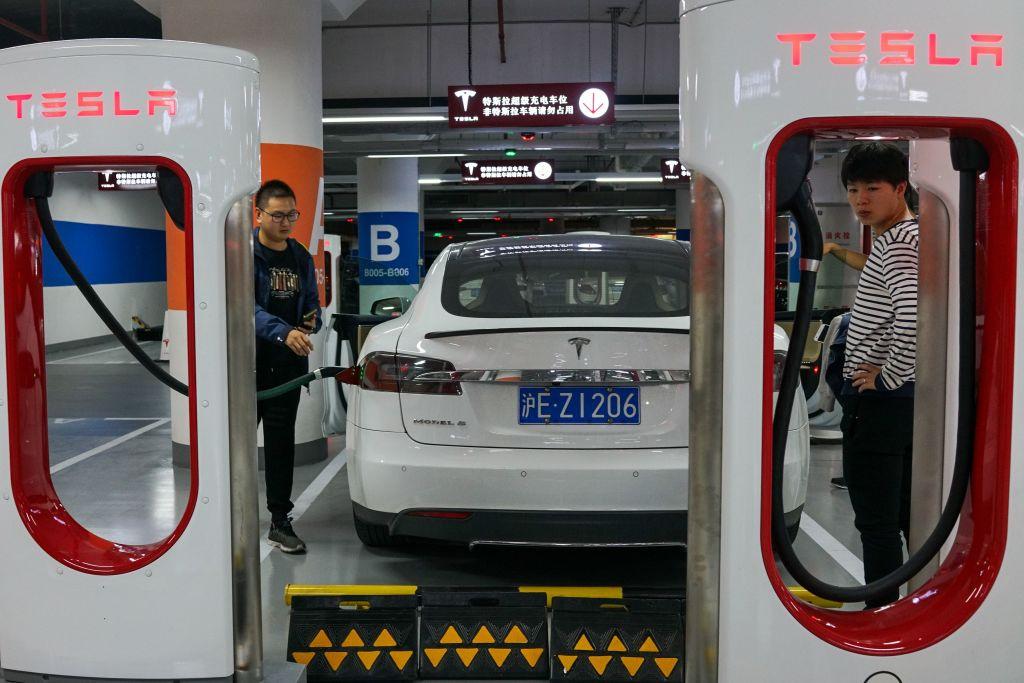 4月19日上午,上海車展首日,一名身穿「剎車失靈」字樣T恤的女子在特斯拉展台鬧場。特斯拉在兩度回應「不妥協」後,遭中共打壓,被迫發表道歉聲明。圖為上海市民在充電站給車輛充電。(CHANDAN KHANNA/AFP via Getty Images)