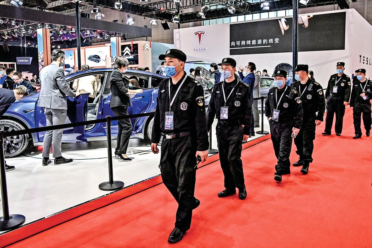 4月19日,在第19屆上海國際汽車工業展覽會上,警衛們從特斯拉汽車展位旁走過。(Getty Images)
