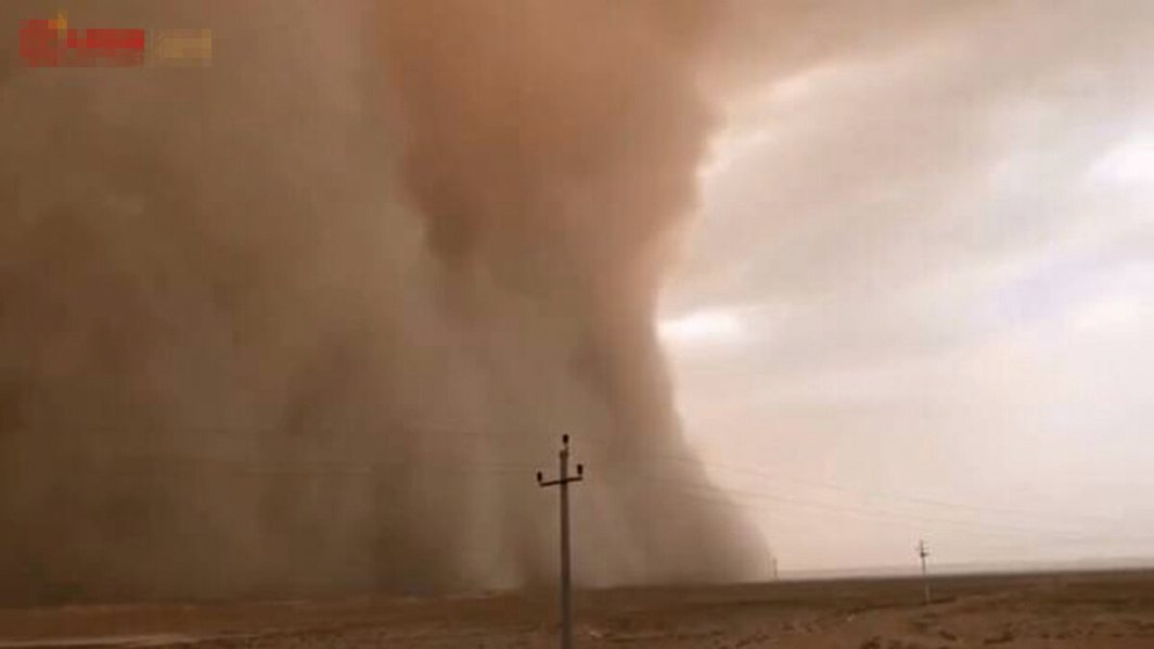 陸媒捕捉到高達數十米的黃色沙塵牆「吞噬」城鎮的恐怖畫面。(影片截圖)