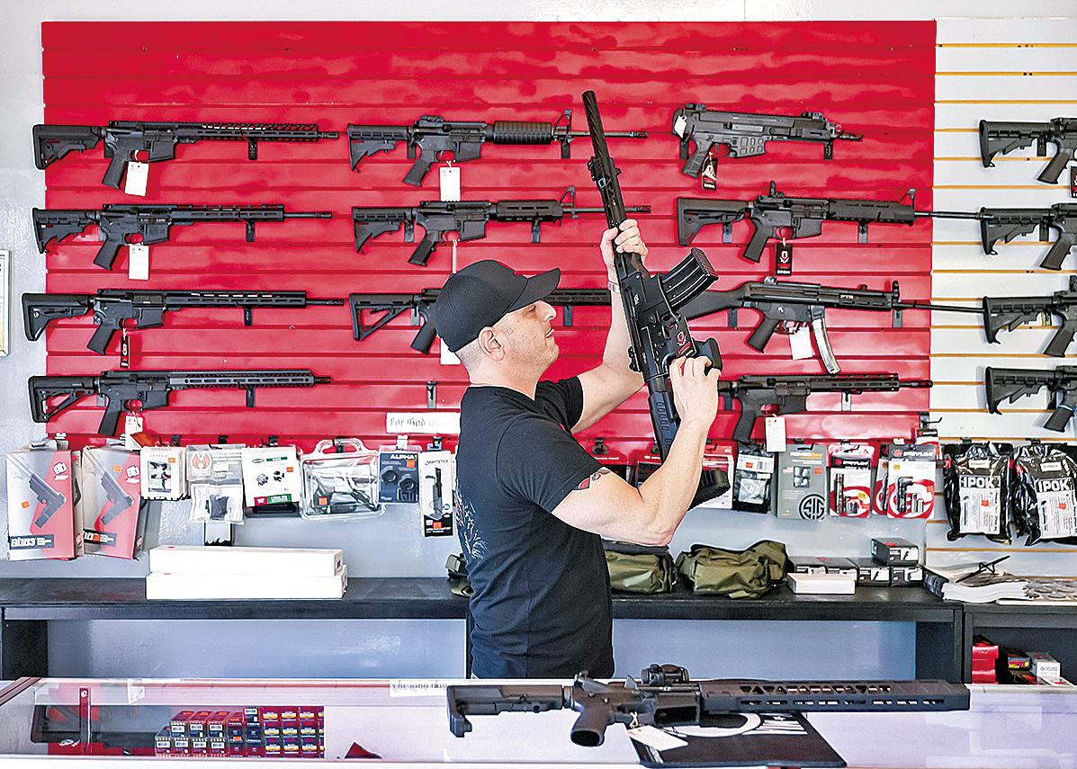 佛州一家槍械商店的工作人員正在幫助顧客檢查槍枝。(Getty Images)