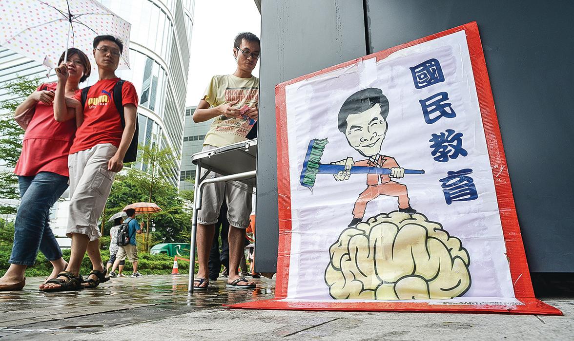 香港街頭貼出的漫畫,就是在譏諷中共在香港強推的國民教育,如同給人洗腦,香港民眾非常反感。(Getty Images)