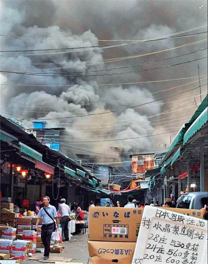 濃煙滾滾的火場不遠處還在進行交易。(Sylvian Wong/Facebook擷圖)