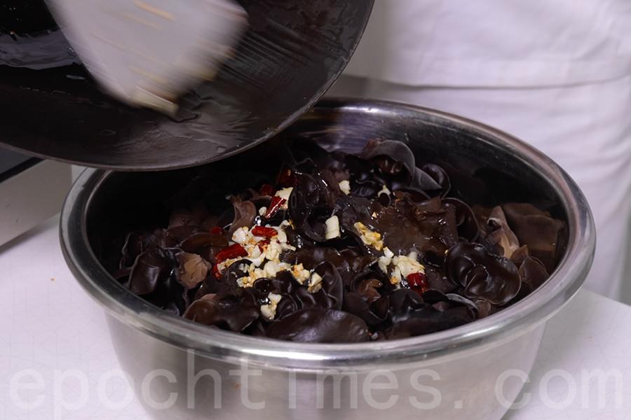 將切好的青瓜和雲耳倒在一個大盆中,倒入爆香的指天椒和蒜蓉。(陳仲明/大紀元)