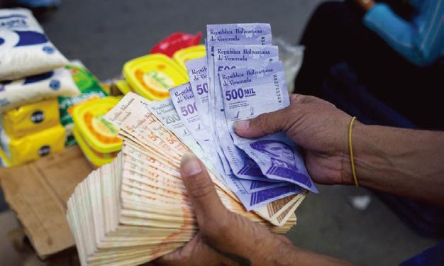 4月6日,一名男子在加拉加斯的卡蒂亞社區的一個街頭市場拿著一疊玻利瓦鈔票。(Getty Images)