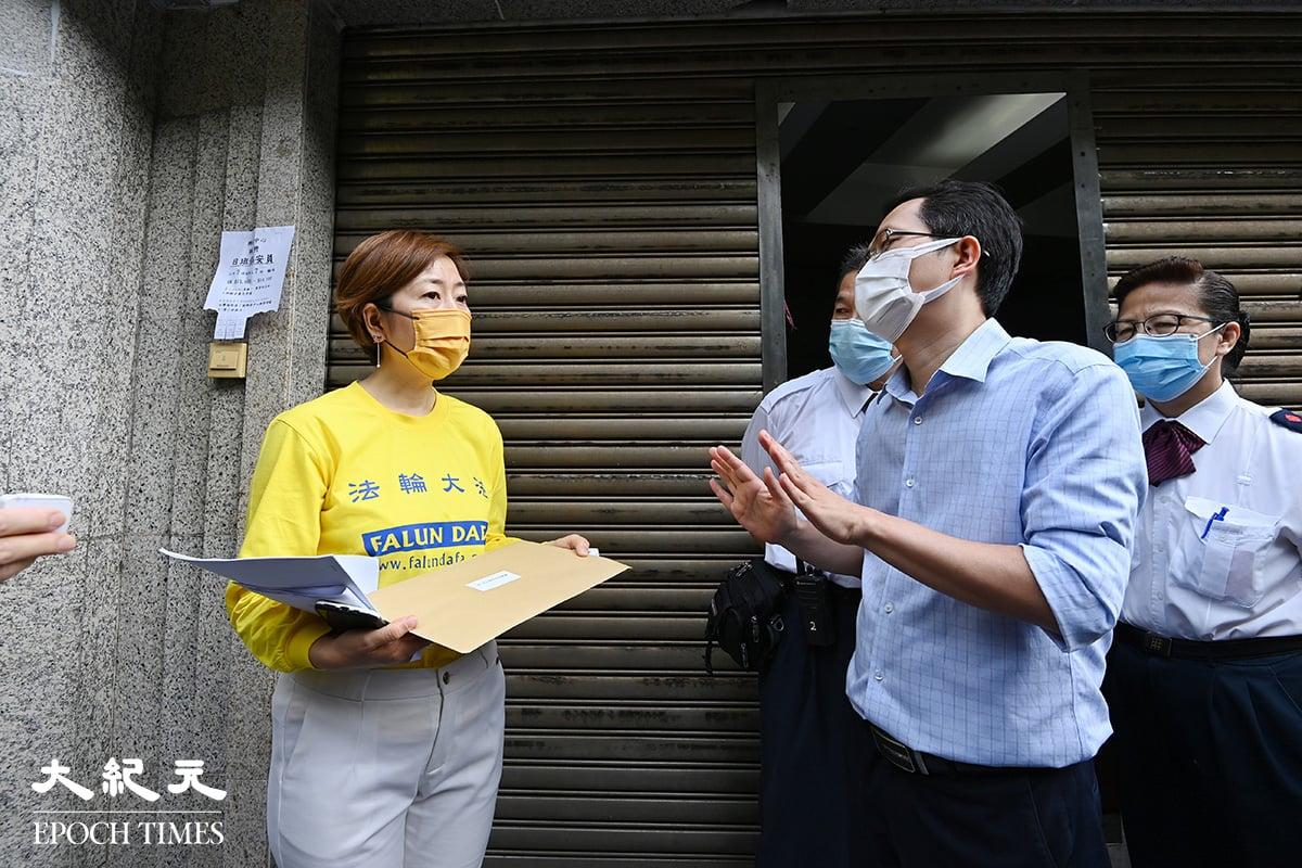 香港法輪佛學會會長梁珍遞信給大公報代表,該名代表擺手不敢接受信件。(宋碧龍/大紀元)