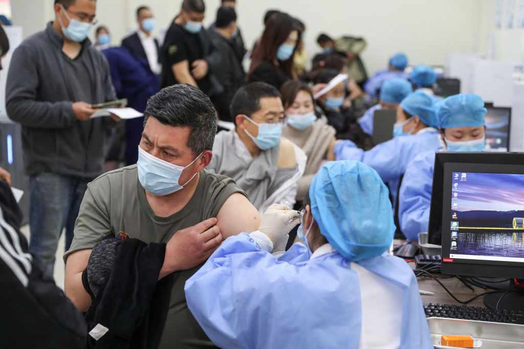 中共當局正極力推動民眾接種國產中共病毒(武漢肺炎)疫苗,為完成這一政治任務,許多地方使出各種手段。圖為江蘇連雲港市民在排隊接種科興疫苗。(STR/AFP via Getty Images)