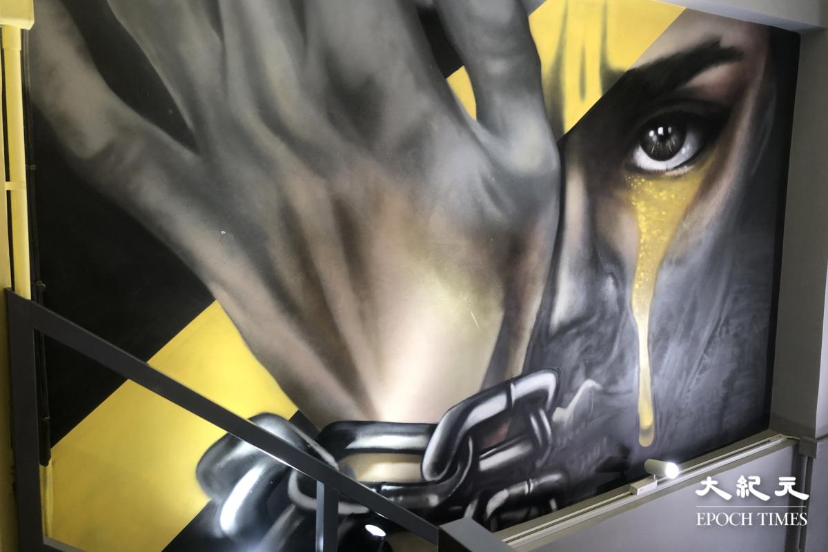 三大 IG-able 打咭位:巨型畫作;畫中人左眼流著黃色眼淚,右手蓋著右眼及一條黃色絲帶,同時手腕上纏有鐵鍊。(謝恩慈/大紀元)