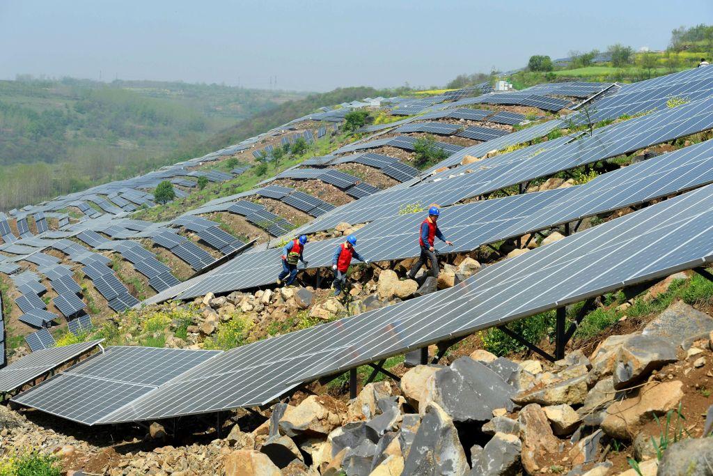中共把過剩的太陽能發電產能,用於對偏遠地區農民的扶貧上,但貸款安裝的農民卻無法償還貸款。圖為中國工人在一個偏遠的山區檢查太陽能面板。(STR/AFP)