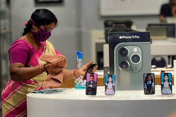 印度嚴重的疫情已經影響到當地的中國企業手機產能。圖為印度清奈一間蘋果手機商店的店員正在進行消毒作業。(ARUN SANKAR/AFP)
