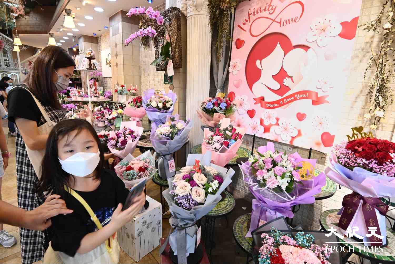 今日(5月9日)是母親節,有父母帶年幼子女一同購買花束送給媽媽及婆婆。(宋碧龍/大紀元)
