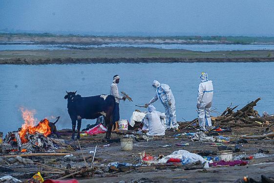 5月5日,印度人身穿防護服在恆河岸邊焚燒染疫病亡的家人屍體。(AFP)