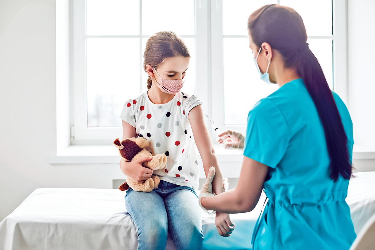一些專家認為給兒童接種COVID-19(中共病毒)疫苗沒有科學依據。圖為醫護工作人員給一名兒童注射。(shutterstock)