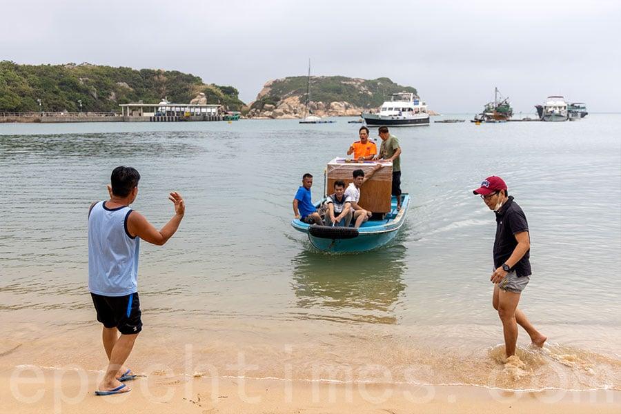 到達蒲台島後,村民將模型轉至接駁小艇送到靠近蒲台公所的沙灘。(陳仲明/大紀元)