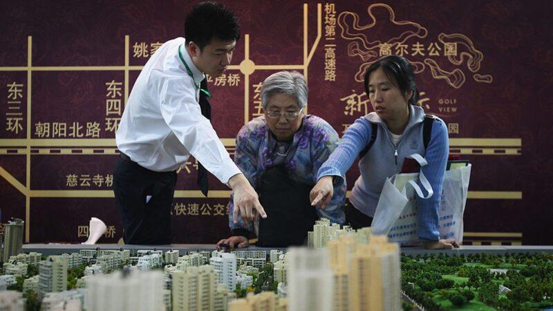 2009年4月8日,北京某房地產銷售人員在向客戶介紹樓盤。(Feng Li/Getty Images)