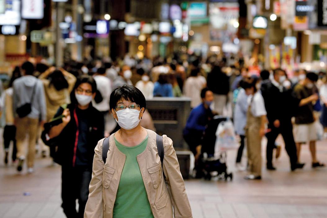 5月8日,在日本神戶,一名戴著口罩的婦女沿著一條商業街行走。(Getty Images)