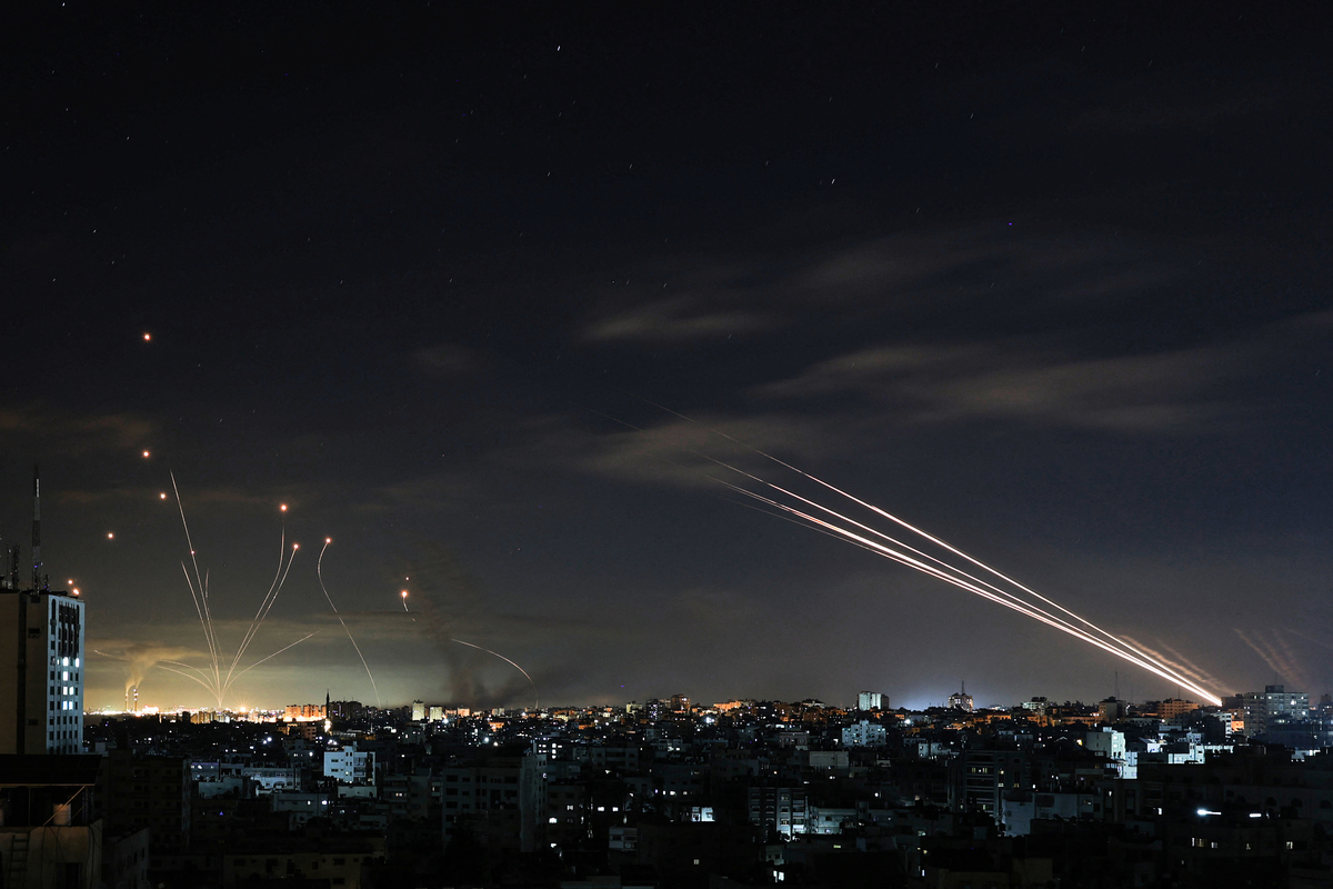 5月16日,以色列的鐵穹導彈防禦系統(左)攔截了哈馬斯恐怖組織從加沙向以色列發射的火箭彈(右)(MOHAMMED ABED/AFP via Getty Images)