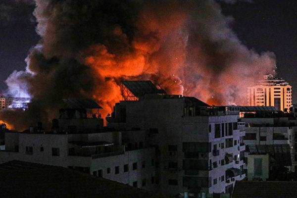 以巴軍事衝突持續,國際社會呼籲停火,以軍方透露目前已擊斃百餘名恐怖份子。圖為2021年5月18日,以色列戰機瞄準加沙地帶一幢政府大樓,進行空襲,以回應加沙地帶恐怖組織哈馬斯(Hamas)發射來的火箭彈。(Fatima Shbair / Getty Images)