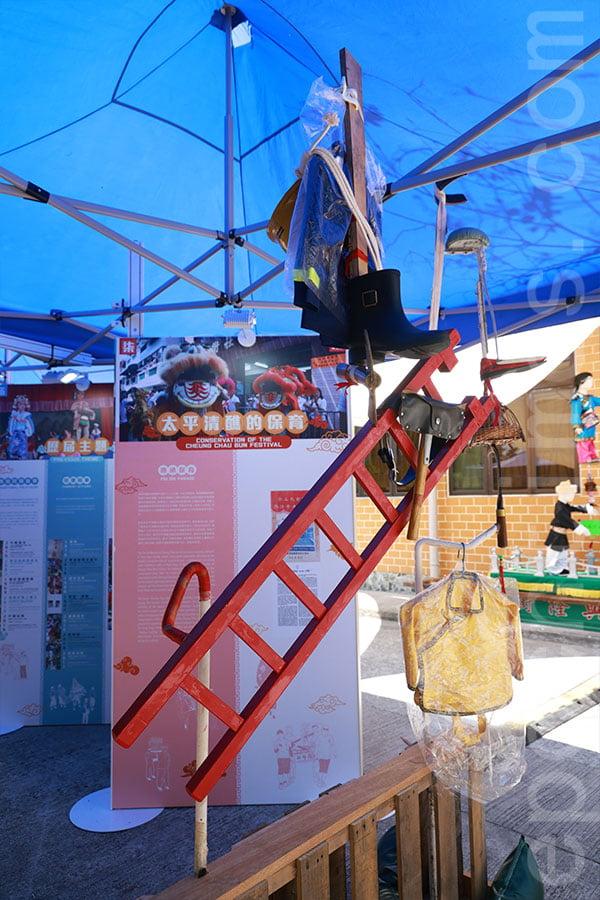 一張斜放的木梯,梯上砍着一把斧頭,色芯再踏在斧頭柄上,製造一種令人嘖嘖稱奇的視覺效果,充份展現飄色師傅的精湛技藝。(陳仲明/大紀元)
