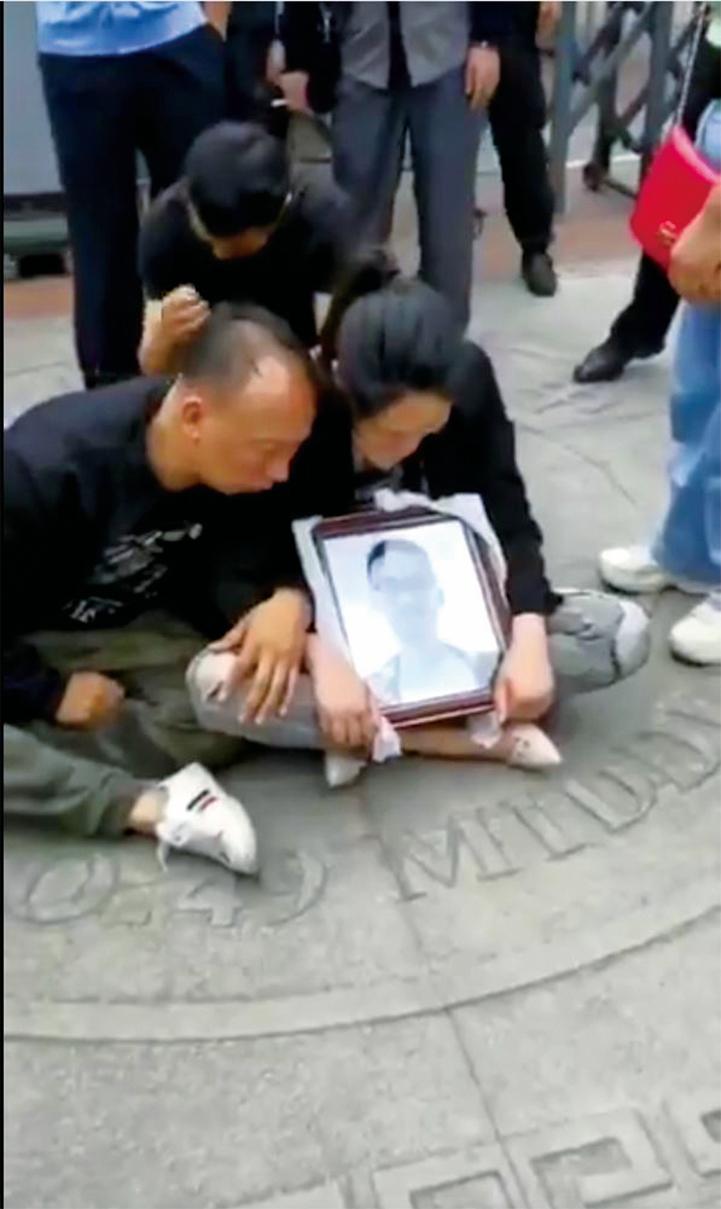 無助的家長在學校門口捧著兒子的遺像抗議。(影片截圖)