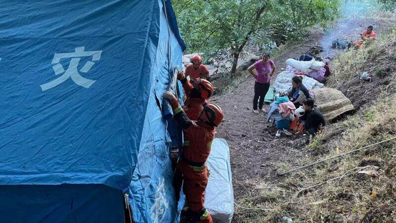 2021年5月22日,在中國雲南省西南部的大理州漾濞縣發生的地震,流離失所的人們在路邊等待進入臨時帳篷。(STR/AFP via Getty Images)