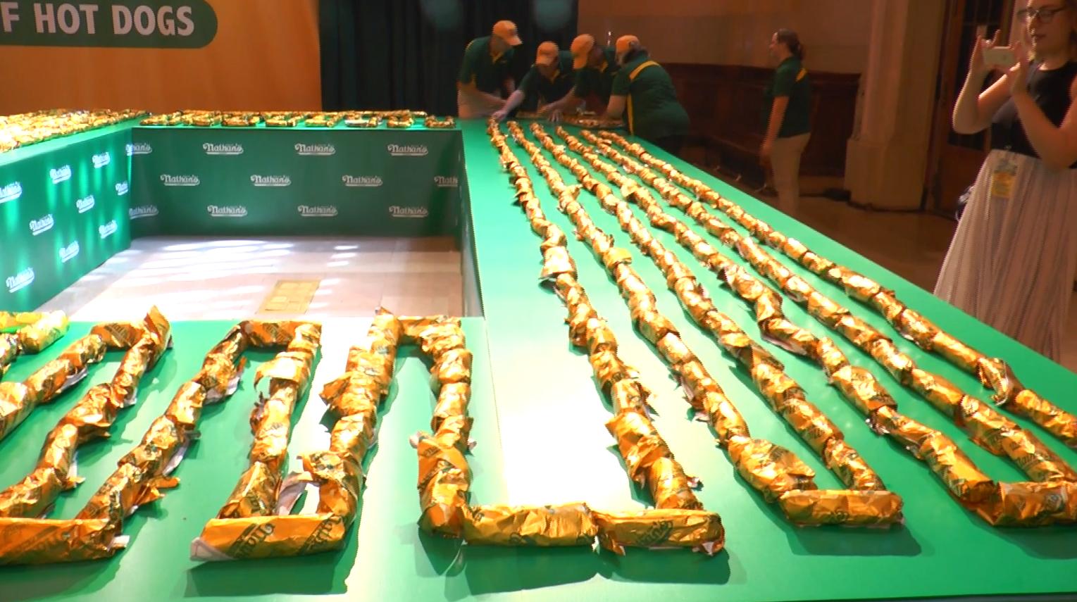 一個個熱狗連著排放起來,成了世界上最長的熱狗串。(韓瑞/大紀元)