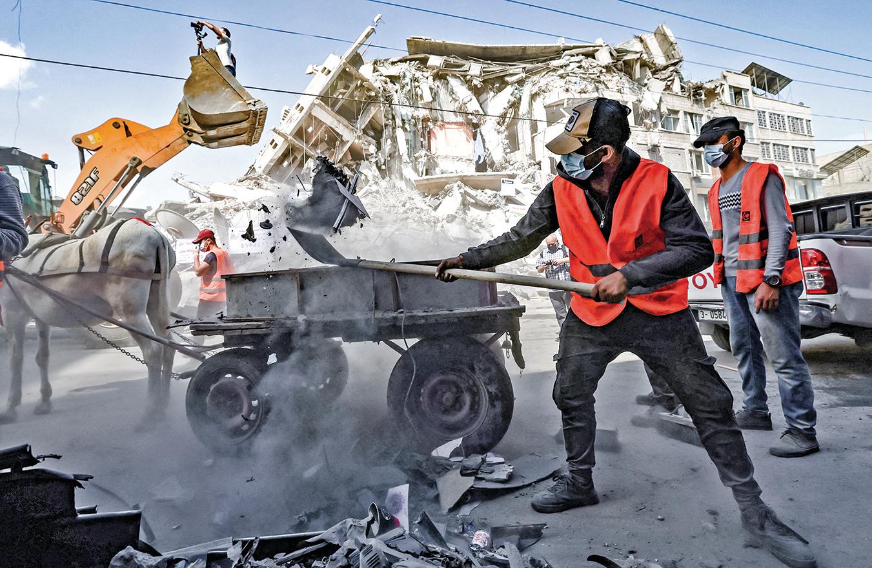 巴以衝突停火之後,巴勒斯坦志願者在清理加沙市商業區的街道。(Getty Images)
