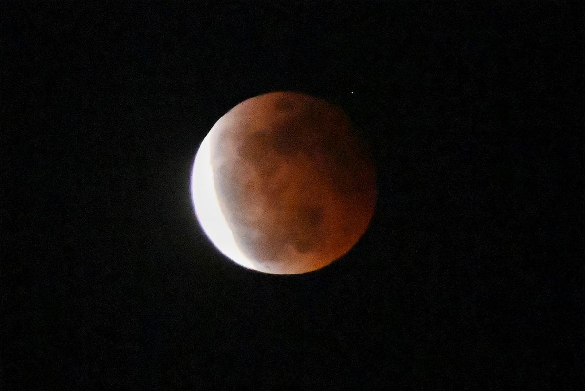 「超級血月」昨晚降臨,月亮在7時多出現時已經開始月食,且呈現偏紅色。這次也是全年最大滿月,月亮直徑比平日大7%。錯過今次月全食與「超級月亮」的雙重天文現象,要等到2033年才可再看見。(圖:宋碧龍/大紀元)