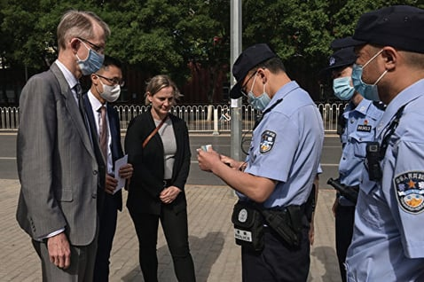 為中共警察在法庭外檢查澳洲駐華大使傅關漢(Graham Fletcher)的證件。(NICOLAS ASFOURI/AFP via Getty Images)