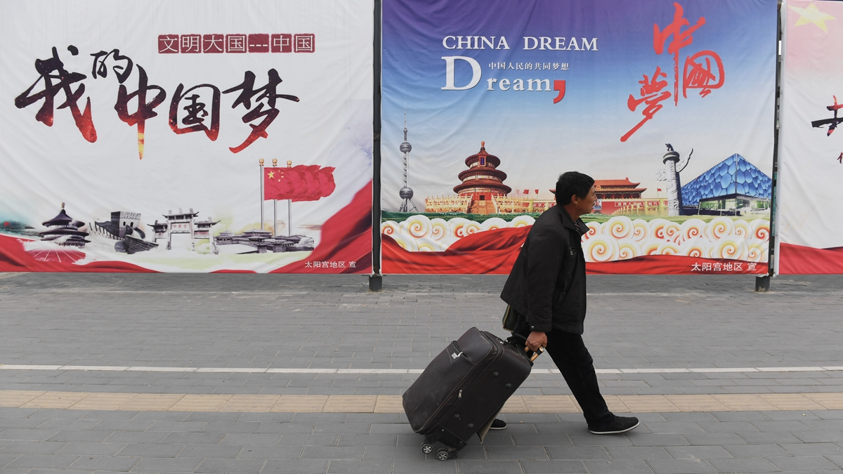 圖為在北京,一名男子走過宣傳「中國夢」的廣告牌,這是與習近平相關的口號。(GREG BAKER/AFP via Getty Images)