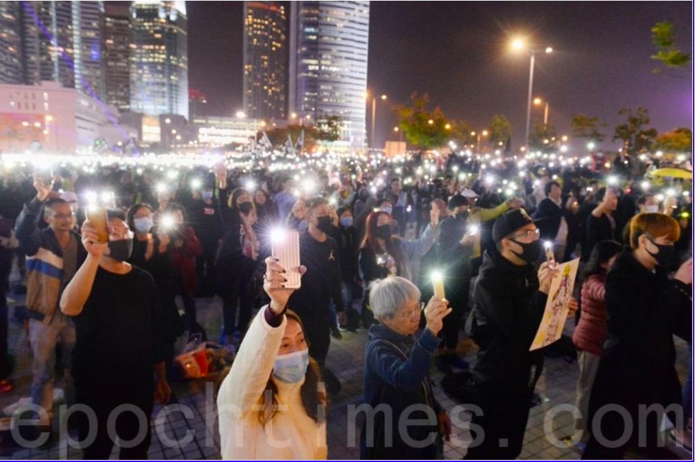 香港政府6月1日通過決定,要求電話智能卡必須實名登記。專家表示,中共是把它在大陸的經驗移植到香港,要把香港大陸化。圖為2019年6月,香港市民持手機在香港警察總部外聚集抗議,反對港府修訂《逃犯條例》(又稱送中條例)。(大紀元資料圖片)