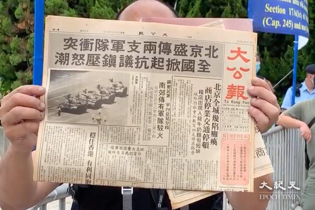 有男子今(6月4日)在維園展示32年前大公報報紙,頭條題為「北京盛傳兩支軍隊衝突 全國掀起抗議鎮壓怒潮」。(黃瑞秋/大紀元)