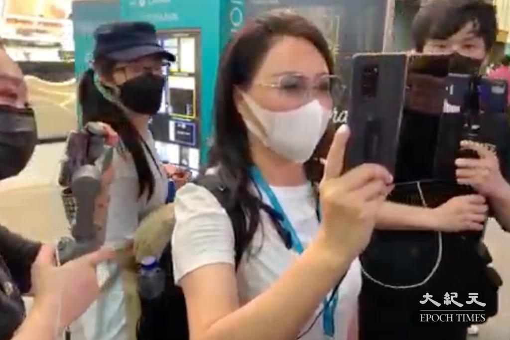 6月4日晚上7時40分左右,本報記者在銅鑼灣發現一位身穿白衣,掛著藍色、有標誌郵輪的牌的女士,到現場用一個螢幕非常大的手機,在拍攝在場記者。(黃瑞秋/大紀元)