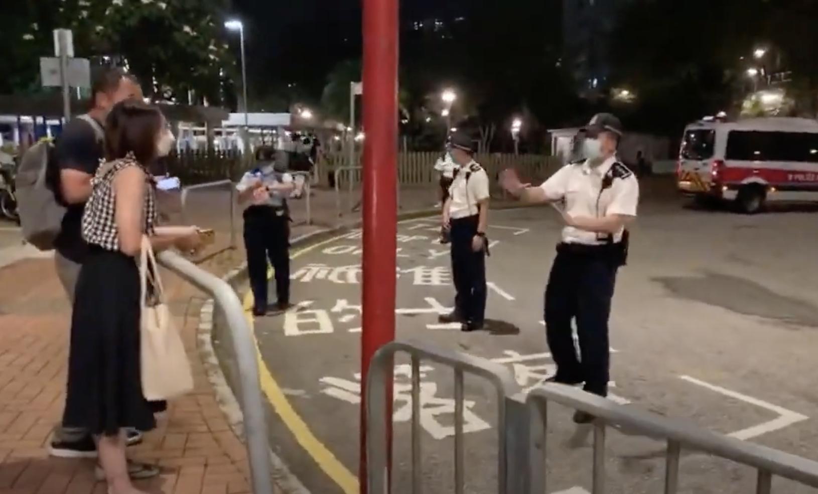 6月4日晚間,有兩位市民站在聖安德肋堂門外街邊等候,幾位白衣警員向這兩位市民大聲勸籲不要違反限聚令。(視頻截圖)