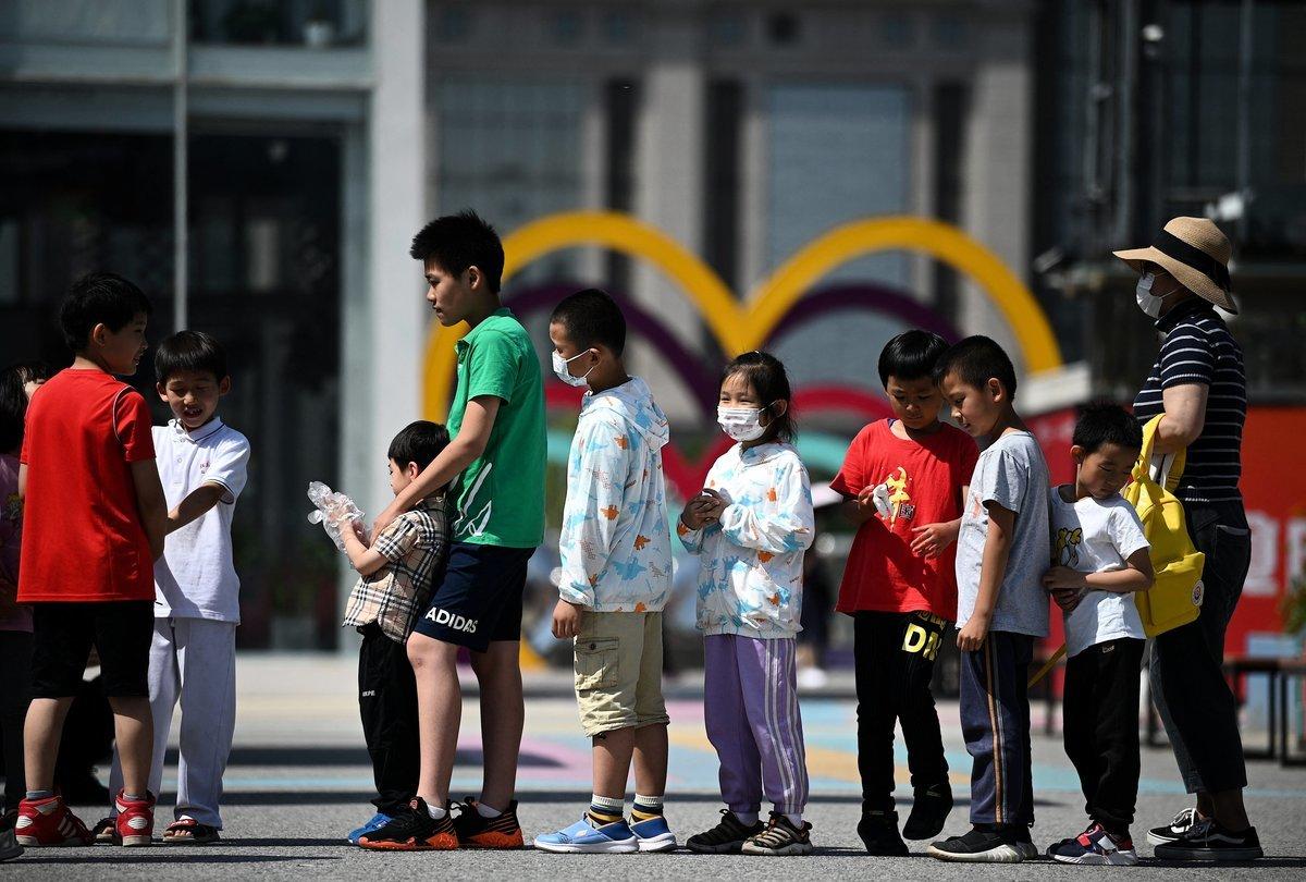 5月31日,北京政府宣佈將允許一對夫婦生育三個孩子。圖爲6月1日北京兒童排隊玩滑梯的情景。(NOEL CELIS/AFP via Getty Images)