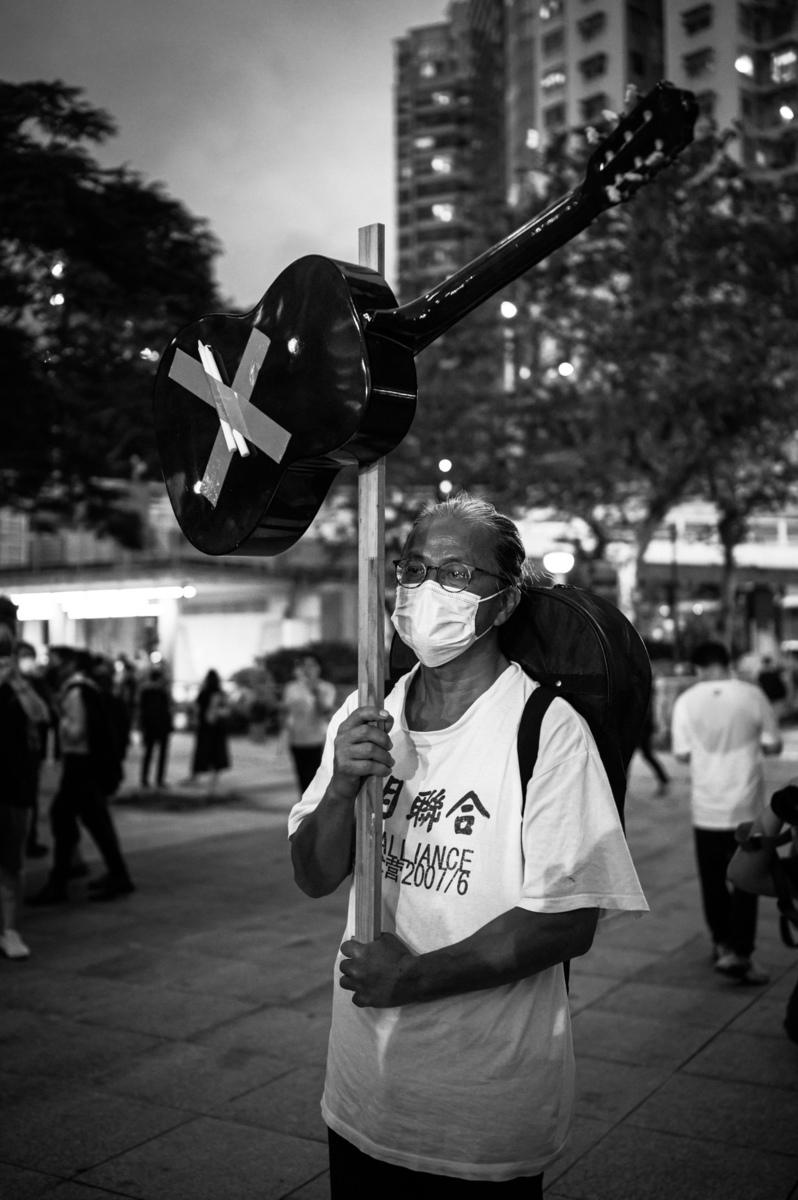 陳先生穿著的白色短袖衫上面寫了「六月聯合」「2007/6」等字,代表2007年6月,六四倖存者和死難者的家屬,找了64名行為藝術家,做了一場紀念六四事件活動的營衣。(潘志雄提供)