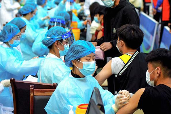 到6月1日,中國大陸已經有兩款疫苗被納入世衛組織的緊急使用清單,但接種中國大陸疫苗的國家,經常會發現有效性和安全性問題。圖為3 月 30 日醫務人員  在中國山東省青島市的一所大學中註射科興毒疫苗。 (STR/AFP )
