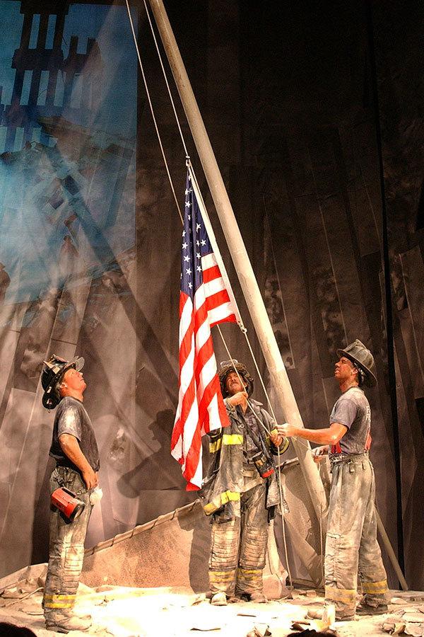 15年前911恐怖襲擊,3名紐約消防隊員在倒塌的世貿大樓廢墟,舉起一面美國國旗。(Spencer Platt/Getty Images)