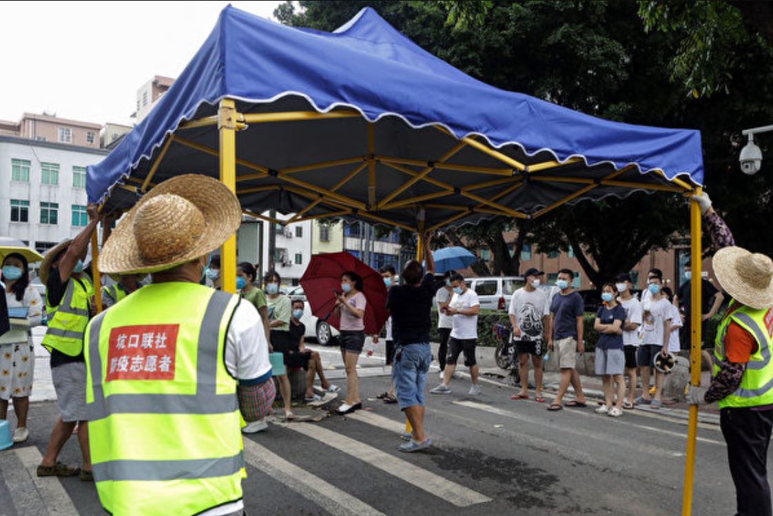 2021年5月30日,廣州市的居民排隊在臨時搭建的帳篷裡準備接受中共病毒核酸檢測。(STR / AFP via Getty Images)