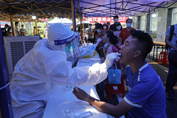 中共病毒在廣州、深圳等地先後爆發,隨後廣東各地都出現病例。隨著廣東疫情持續延燒,中國經濟復甦或受影響。圖為5月30日廣州民眾接受核酸檢測。 (STR/AFP via Getty Images)
