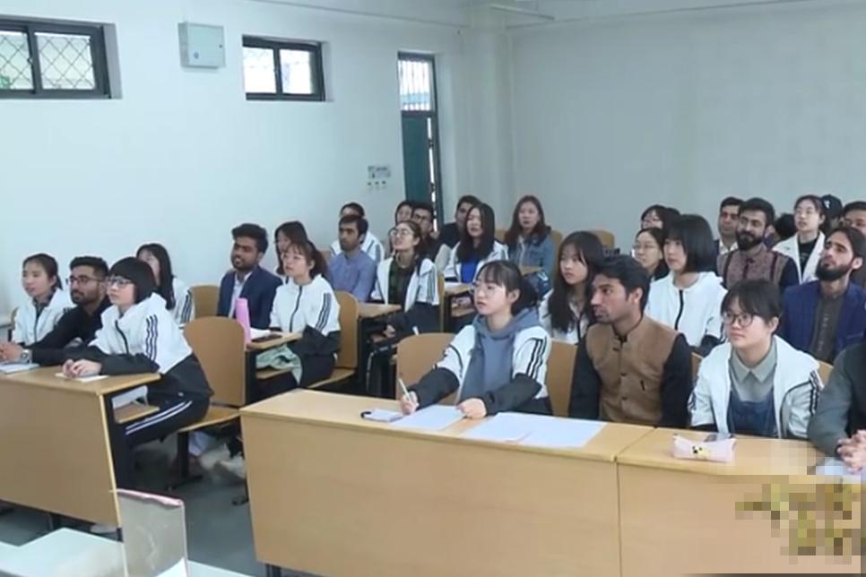 河北師範大學的一張教學圖片顯示,每名外籍男留學生身旁,都配有一名或兩名中國女大學生,此圖片引發輿論爭議。(視頻截圖)
