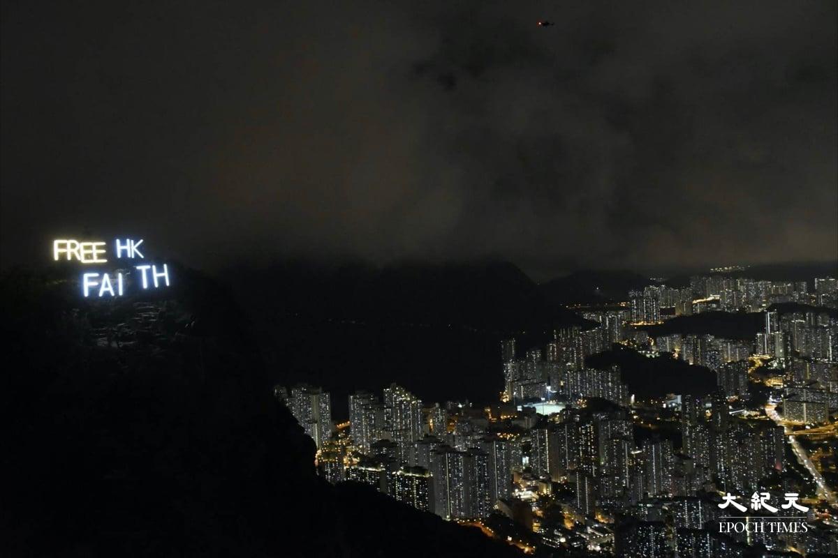 左邊獅子山上的FREE HK與右邊的九龍燈光交相輝映。(麥碧/大紀元)