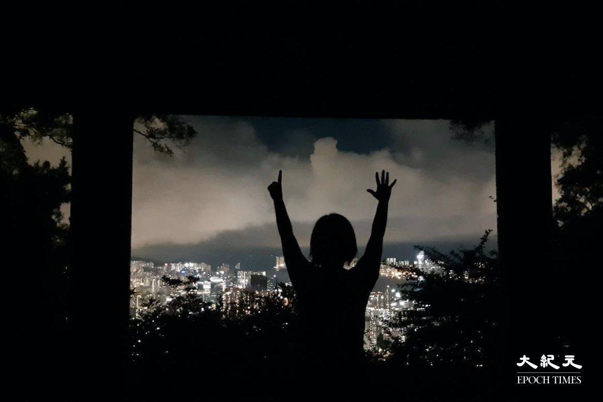 有市民在觀景亭舉起「五一」手勢。 ( 麥碧/大紀元)