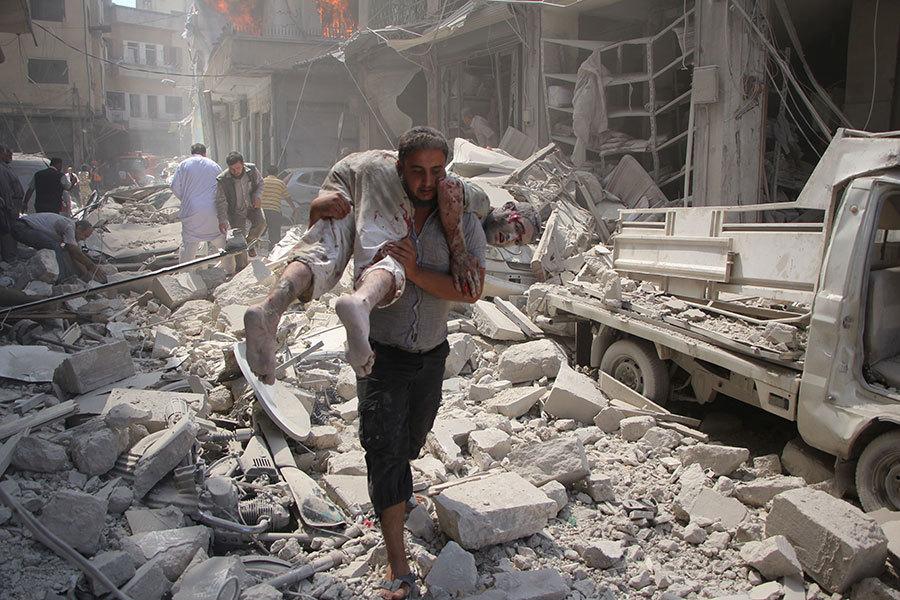 美俄於2016年9月10日宣佈促成敘利亞停火協議,但敘利亞北部的兩大城在同日仍遭密集的砲彈攻擊,已造成至少百人死亡。本圖為伊德利布市的熱鬧地區遭到攻擊後,救援人員從殘骸中抬出傷者。(OMAR HAJ KADOUR/AFP/Getty Images)