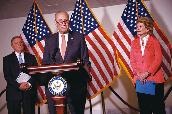 2021年6月8日,美國參議院多數黨領袖查理斯舒默(中)與參議員理查德德賓(左)和參議員黛比斯塔貝諾(右)在參議院民主黨午餐會後出席新聞發佈會。(Kevin Dietsch/Getty Images)