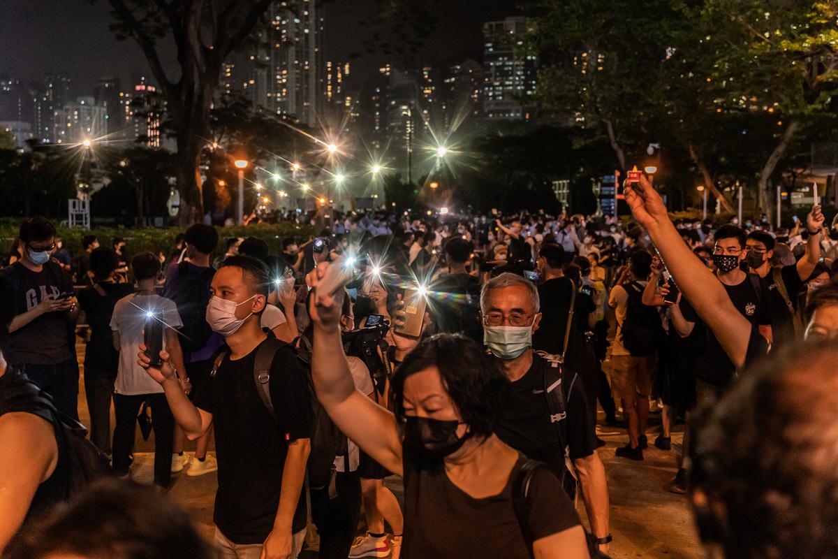 今年6月4日,警方封閉了支聯會歷年舉辦燭光晚會的維園,但是並未能阻止市民在街上流動悼念,許多悼念六四的群眾舉著手機燈光圍著維園行街。(Anthony Kwan/Getty Images)
