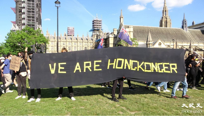 集會人士在議會廣場手持「我們是香港人」的橫額。(文苳晴/大紀元)