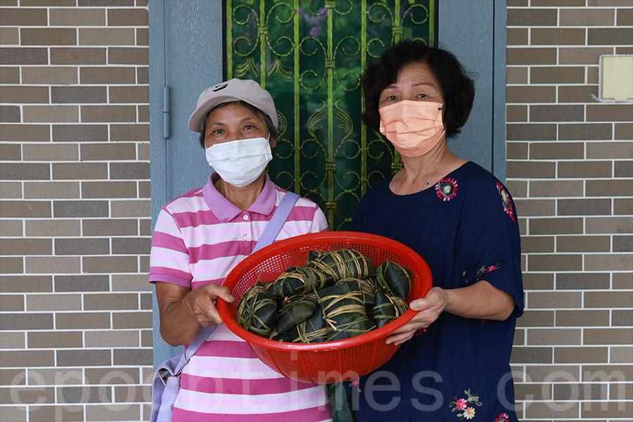 元崗村梁太(右)分享她們圍頭五角糭的包糭心得,客家人萍姐前來學習之餘,亦分享了她的客家糭包紮方式。(陳仲明/大紀元)