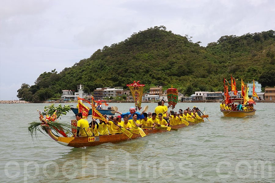 傳統龍舟拖著載有神像的神艇在大澳水道巡遊,以潔淨社區,祈求平安。(陳仲明/大紀元)
