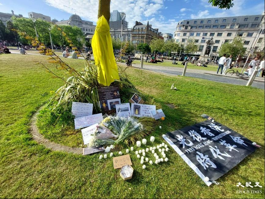 出席悼念活動的港人在公園一棵樹幹上掛起象徵梁凌杰墮樓前的黃色雨衣,地上又擺放悼念字句、「光時」旗幟、鮮花和蠟燭。(陳渭新提供)