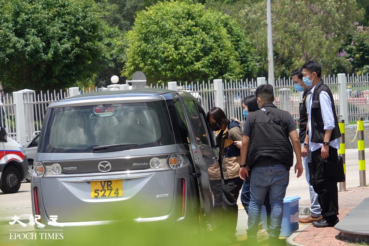 《 蘋果日報》副社長陳沛敏被警員帶離蘋果大樓。( 余鋼/大紀元)